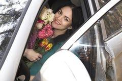 Muchacha hermosa con las flores en el coche Fotos de archivo