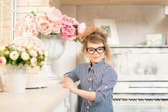 Muchacha hermosa con las flores en el piano Foto de archivo