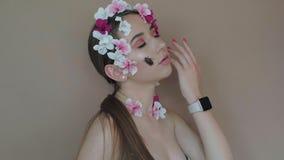 Muchacha hermosa con las flores y el escarabajo del jorobado en la cara que presenta a la cámara almacen de metraje de vídeo