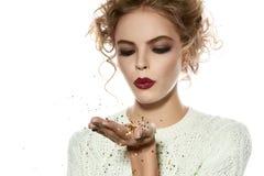 Muchacha hermosa con las lentejuelas del oro del soplo del maquillaje de la tarde Imagen de archivo