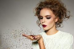 Muchacha hermosa con las lentejuelas del oro del soplo del maquillaje de la tarde Foto de archivo