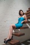 Muchacha hermosa con las piernas largas que mienten en los pasos de madera del s Imágenes de archivo libres de regalías