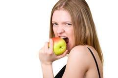 Muchacha hermosa con los corchetes que come la manzana Imagenes de archivo
