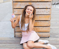Muchacha hermosa con los dreadlocks en la falda rosada que se sienta en el mirador y que come el cono de helado colorido en una t Fotos de archivo