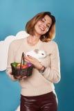 Muchacha hermosa con los huevos blancos del conejito y del color de pascua de la cesta Imagenes de archivo