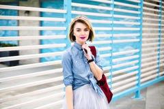 Muchacha hermosa con los labios rosados brillantes y tatuaje en su smartphone de la tenencia de la mano que lleva la camisa azul  imagen de archivo