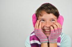 Muchacha hermosa con los manguitos del oído y los guantes cortados Imágenes de archivo libres de regalías