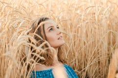 Muchacha hermosa con los ojos azules que se relajan en el campo del verano del trigo Foto de archivo