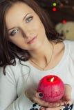 muchacha hermosa con los ojos verdes con una vela roja en su mano imágenes de archivo libres de regalías