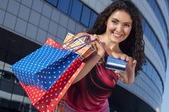 Muchacha hermosa con los panieres y la tarjeta de crédito Imagen de archivo