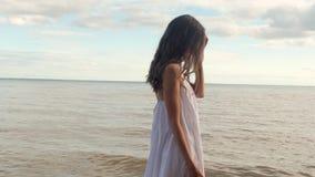 Muchacha hermosa con los pies desnudos que camina en una playa arenosa Sonrisas y giro almacen de video