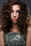 Muchacha hermosa con los rizos y brillo verde en los párpados La mujer modelo con hermoso compone y peinado rizado Fotos de archivo