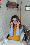 Muchacha hermosa con los vidrios en café imagen de archivo libre de regalías