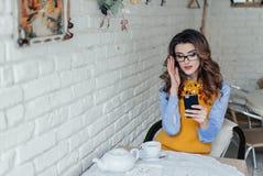 Muchacha hermosa con los vidrios en café Imagenes de archivo