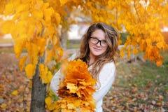 Muchacha hermosa con los vidrios en hojas de otoño amarillas en el parque Imagen de archivo libre de regalías