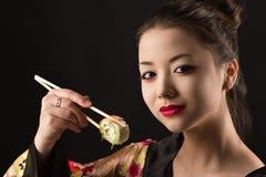 Muchacha hermosa con maquillaje brillante que come el primer del sushi Fotografía de archivo libre de regalías