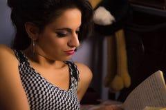 Muchacha hermosa con maquillaje profesional que lee un libro Imagen de archivo libre de regalías