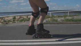 Muchacha hermosa con patinaje sobre ruedas rojo del pelo al aire libre ciérrese encima de las piernas almacen de metraje de vídeo