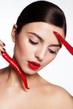 Muchacha hermosa con pimientas de chile rojo calientes Imagen de archivo