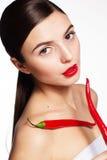 Muchacha hermosa con pimientas rojas calientes de los cayennes Fotografía de archivo libre de regalías