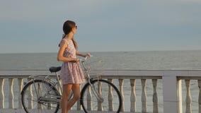 Muchacha hermosa con su bici en el terraplén cerca de una playa almacen de video