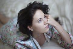 Muchacha hermosa con su pelo en la cama Foto de archivo libre de regalías