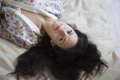 Muchacha hermosa con su pelo en la cama Fotos de archivo