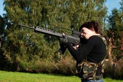 Muchacha hermosa con un arma Foto de archivo libre de regalías