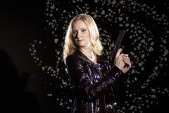 Muchacha hermosa con un arma en su mano Fotos de archivo