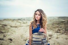 Muchacha hermosa con un birdcage en una duna Fotos de archivo