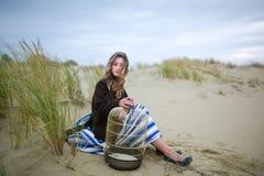 Muchacha hermosa con un birdcage en una duna Fotografía de archivo