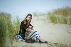 Muchacha hermosa con un birdcage en una duna Imagen de archivo libre de regalías