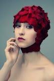 Muchacha hermosa con un casquillo de pétalos color de rosa Foto de archivo