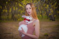 Muchacha hermosa con un conejo blanco Una mujer est? sosteniendo una liebre foto de archivo
