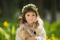 Muchacha hermosa con un conejo en el bosque Foto de archivo libre de regalías