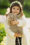 Muchacha hermosa con un conejo en el bosque Foto de archivo