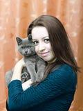 Muchacha hermosa con un gato en las manos Fotos de archivo