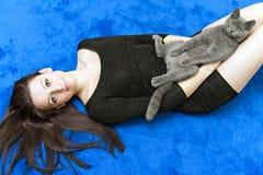 Muchacha hermosa con un gato en las manos Imagen de archivo