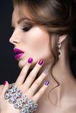 Muchacha hermosa con un maquillaje brillante de la tarde y manicura púrpura con los diamantes artificiales Diseño del clavo Cara  Foto de archivo