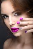 Muchacha hermosa con un maquillaje brillante de la tarde y manicura púrpura con los diamantes artificiales Diseño del clavo Cara  imagen de archivo libre de regalías
