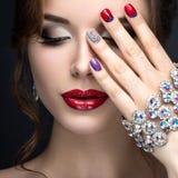 Muchacha hermosa con un maquillaje brillante de la tarde y manicura roja con los diamantes artificiales Diseño del clavo Cara de  imagenes de archivo