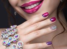 Muchacha hermosa con un maquillaje brillante de la tarde y manicura rosada con los diamantes artificiales Diseño del clavo Cara d imagenes de archivo