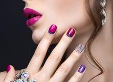 Muchacha hermosa con un maquillaje brillante de la tarde y manicura rosada con los diamantes artificiales Diseño del clavo Cara d Foto de archivo