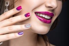 Muchacha hermosa con un maquillaje brillante de la tarde y manicura rosada con los diamantes artificiales Diseño del clavo Cara d Imagen de archivo