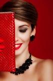 Muchacha hermosa con un monedero rojo maquillaje accesorios Fotos de archivo libres de regalías