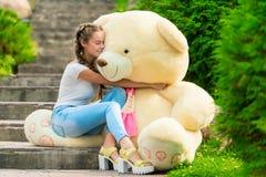 muchacha hermosa con un oso de peluche enorme en el parque Foto de archivo libre de regalías