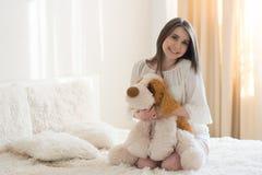 Muchacha hermosa con un perro de la felpa en la cama fotografía de archivo libre de regalías