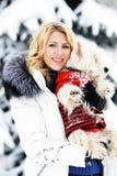 Muchacha hermosa con un perro en la madera del invierno Fotografía de archivo
