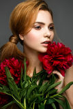 Muchacha hermosa con un ramo de peonías Modelo con un maquillaje apacible Cara de la belleza Imagen de archivo
