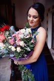 Muchacha hermosa con un ramo grande de flores Imágenes de archivo libres de regalías